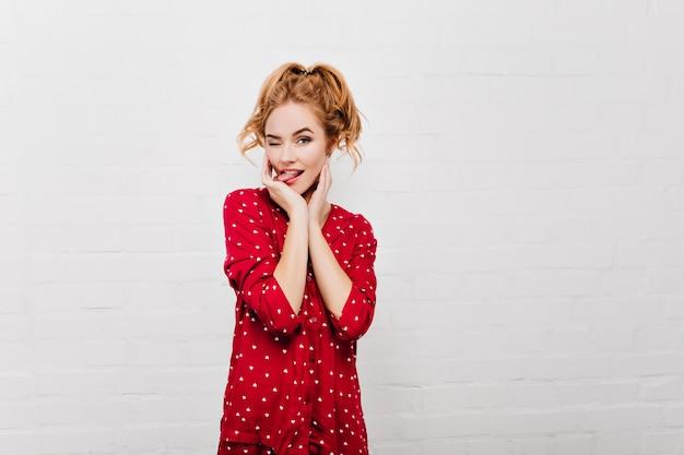 Schöne dame im roten pyjama, die lustige gesichter macht. innenporträt des blonden weiblichen modells im nachtanzug lokalisiert auf weißer wand.
