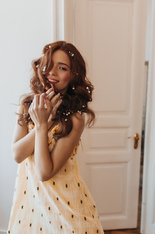 Schöne dame im stilvollen gelben kleid berührt kokett ihr haar und lächelt süß gegen weiße tür.