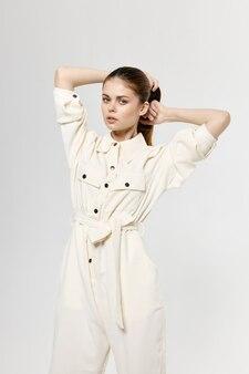 Schöne dame im weißen overall berührt haare auf ihrem kopf mit ihren händen und modischem licht.