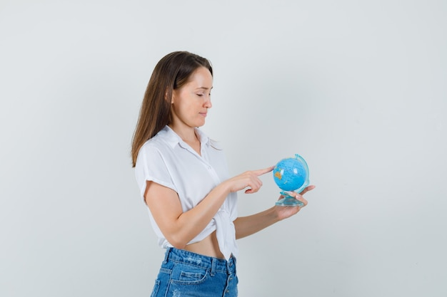 Schöne dame in der weißen bluse, die mini-globus betrachtet und vorsichtig schaut, vorderansicht.