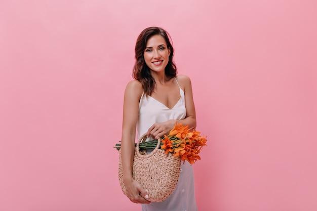Schöne dame in der weißen bluse hält strohsack und orange blumen. hübsche frau im leichten modischen outfit hält gestrickte handtasche mit blumenstrauß.