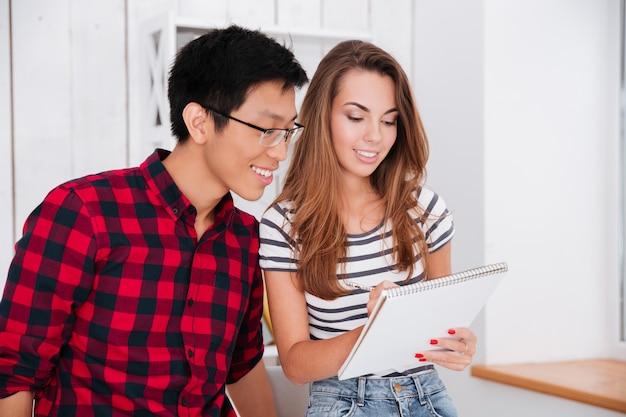 Schöne dame in einem t-shirt mit streifenmuster und jeans, die in ein notizbuch schreibt, und ihr gruppenkamerad mit brille, der ihre notizen betrachtet