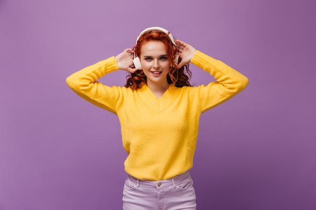 Schöne dame in gelbem pullover und kopfhörern posiert über lila wand