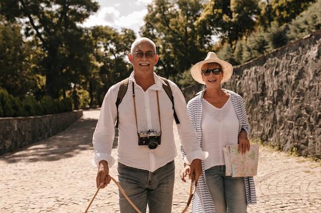Schöne dame in sonnenbrille, hut und gestreifter bluse lächelnd und posierend mit mann mit schnurrbart im weißen hemd und in jeans mit kamera im freien.