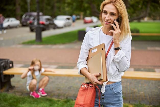 Schöne dame in weißem hemd und jeans, die einen ordner mit einem dokument in der hand hält, während sie im stadtpark steht