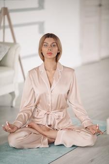 Schöne dame meditiert auf dem boden in ihrem schlafzimmer