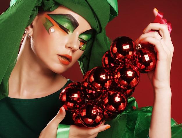 Schöne dame mit dem künstlerischen make-up, das weihnachten decoratio hält