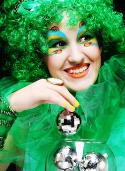 Schöne dame mit dem künstlerischen make-up, das weihnachtsdekoration hält