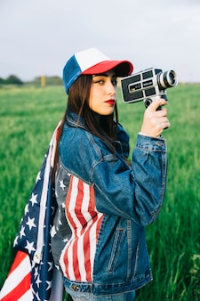 Schöne dame mit der retro- kamera, die auf dem gebiet bleibt