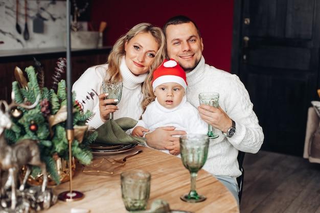 Schöne dame mit ihrem mann und kind, die am weihnachtstisch sitzen