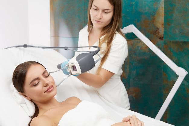 Schöne dame mit perfektem gesicht, die kosmetikverfahren mit laser durch kosmetikerin tut