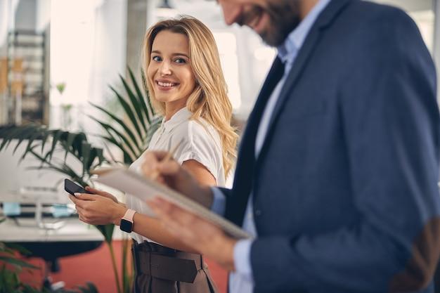 Schöne dame mit smartphone, die kamera anschaut und lächelt, während der mann im notizbuch schreibt