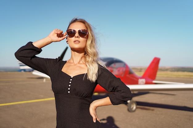 Schöne dame mit sonnenbrille posiert in der nähe des flugzeugs