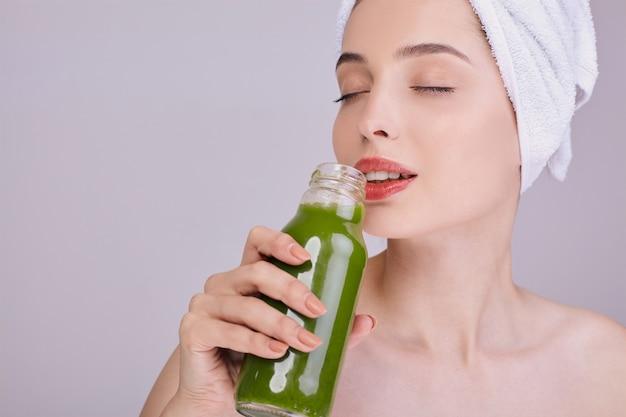 Schöne dame nach einer dusche genießt einen grünen smoothie in einer flasche.