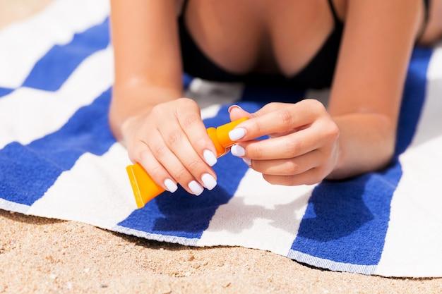 Schöne dame nimmt ein sonnenbad auf dem handtuch im sand am strand und schützt ihre hände mit sonnencreme