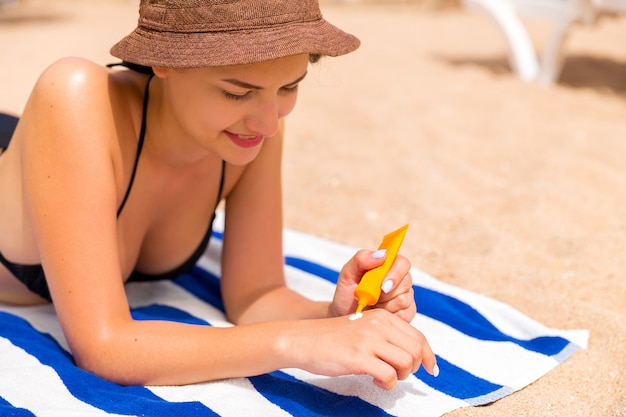 Schöne dame sonnt sich auf dem handtuch im sand am strand und schützt ihre hände mit sonnencreme.