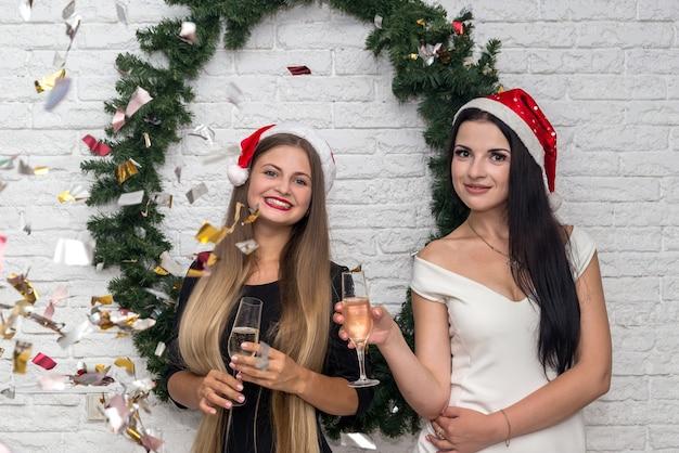 Schöne damen mit champagner und weihnachtsmützen