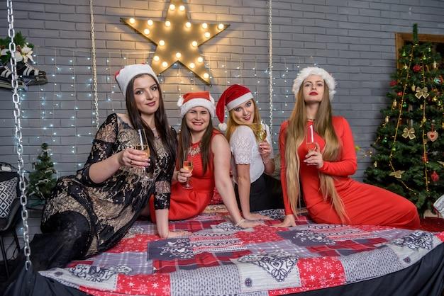 Schöne damen mit champagnergläsern, die in der nähe des weihnachtsbaums sitzen