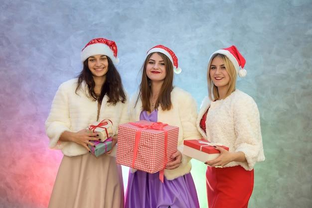 Schöne damen mit geschenkboxen in modischen abendkleidern und weihnachtsmützen