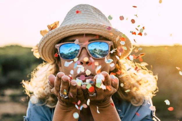 Schöne defokussierte frau bläst konfetti aus den händen. feier- und veranstaltungskonzept. glück und farbiges bild. bewegung und glück für aktive menschen lifestyle und freude