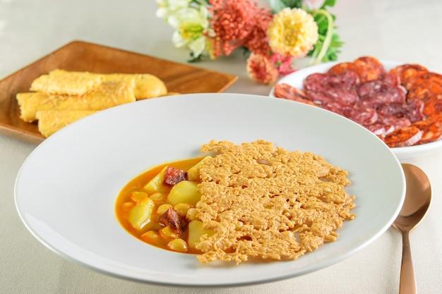 Schöne dekoration des tisches. weißer moderner teller mit suppensauce von kartoffeln