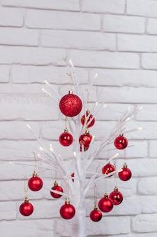 Schöne dekorative weiße zweige mit weihnachtsspielzeug