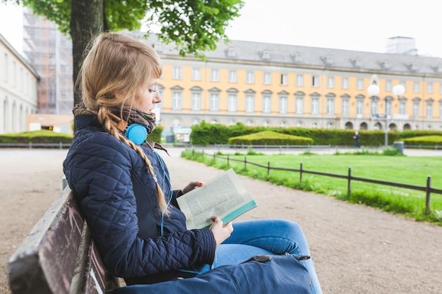Schöne deutsche frau, die ein buch am park liest