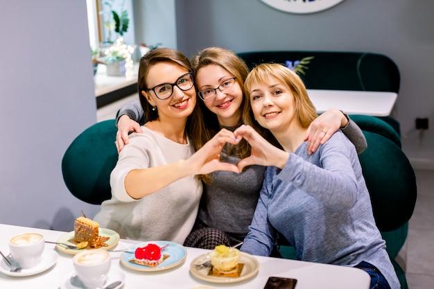 Schöne drei junge frauen, die eine schale schwarzen kaffee mit köstlichen nachtischen, lächelnd in der liebe zeigt herzsymbol und -form mit den händen trinken. romantisches konzept.