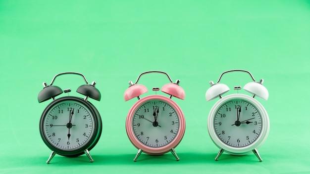 Schöne drei wecker auf grünem bildschirm hintergrund wecker gesicht tagsüber minimal wecker konzept zeitzone.