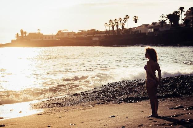 Schöne dünne frau kaukasier, die am ufer in der nähe von meereswellen steht, um urlaub und freien lebensstil in kontakt mit der natur zu genießen horizont und sonnenuntergang. füße im sand und glück im sommer