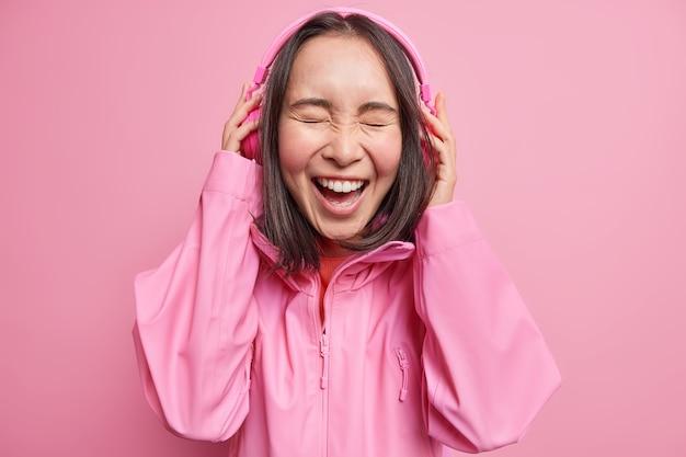Schöne dunkelhaarige asiatische frau hört lustige geschichte online über stereo-kopfhörer lacht glücklich schließt die augen vor freude trägt jacke isoliert über rosa wand. menschen emotionen lifestyle-konzept