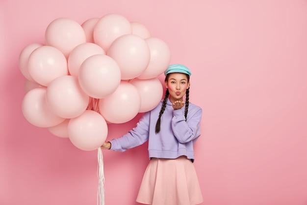 Schöne dunkelhaarige dame mit spezifischem aussehen, trägt make-up, hält die lippen gerundet, bläst luftkuss in die kamera, hat flirtenden ausdruck, posiert mit heliumballons, isoliert über rosa wand