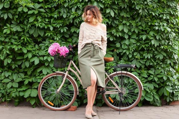 Schöne dunkelhaarige frau in der strickjacke und im beige rock lächelnd, aufwerfend und nahe bei einem fahrrad stehend.