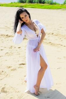 Schöne dunkelhaarige frau in einem badeanzug am strand. porträt, haltung, blick.