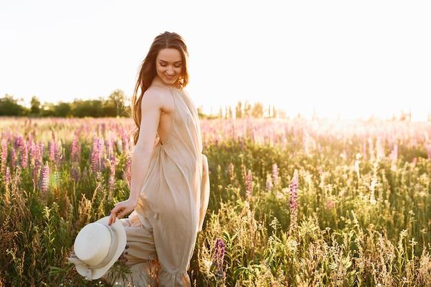 Schöne dunkelhaarige frau in einem sommerkleid auf einem gebiet von blühenden lupineblumen