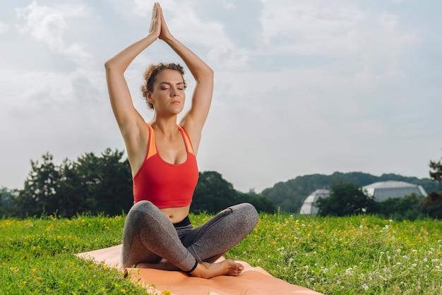 Schöne dunkelhaarige yoga-frau, die ruhe und freiheit in der natur schätzt