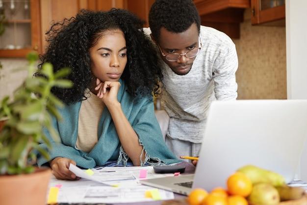 Schöne dunkelhäutige junge frau mit afro-frisur, die besorgtes aussehen beim verwalten des familienbudgets hat