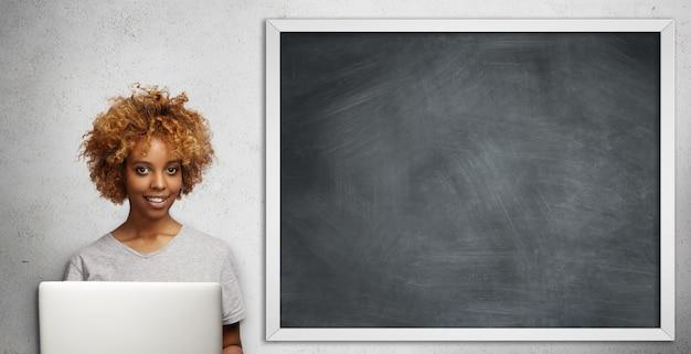 Schöne dunkelhäutige junge lehrerin mit stilvollem haarschnitt, der papiere ihrer schüler prüft, mit laptop im klassenzimmer