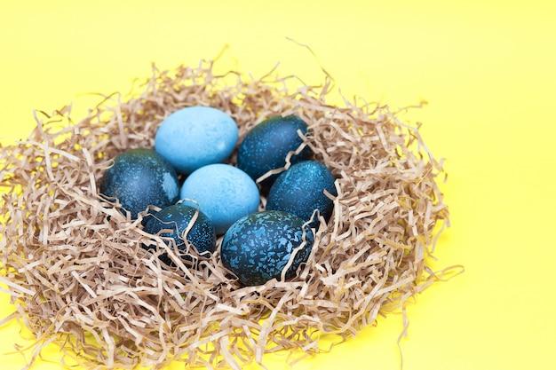 Schöne dunkle ostereier liegen in einem nest auf gelbem grund