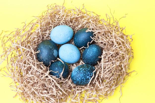 Schöne dunkle ostereier liegen in einem nest auf gelbem hintergrund, draufsicht