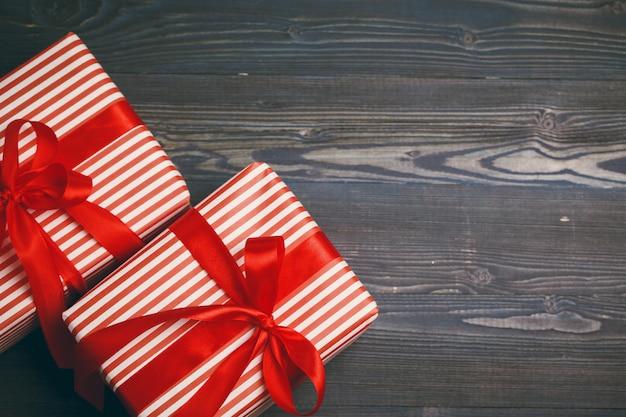 Schöne eingewickelte geschenke auf dunklem hölzernem hintergrund