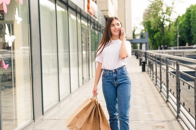 Schöne einkaufsfrau, die auf ihrem handy spricht, das mit taschen auf der straße geht