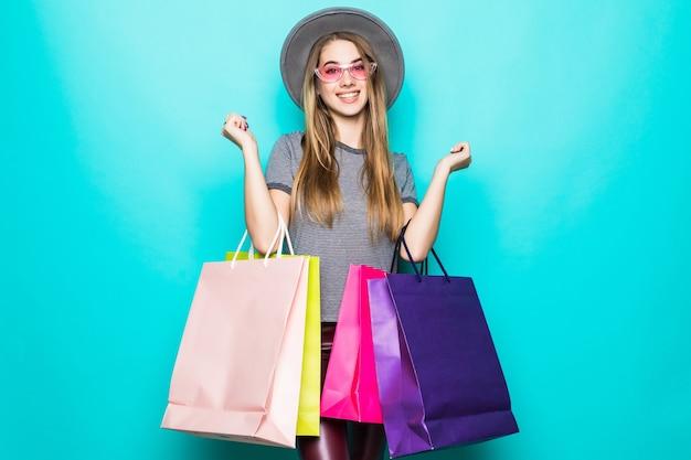 Schöne einkaufsfrau lächelnd und einen hut getragen über grünem hintergrund