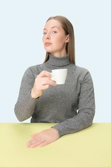 Schöne einsame frau, die am blauen studio sitzt und traurig schaut, die tasse kaffee in der hand haltend. nahaufnahme getöntes porträt im minimalismusstil