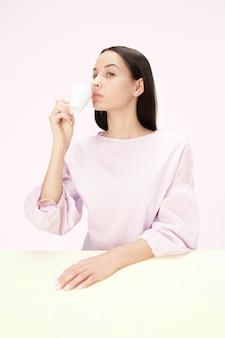 Schöne einsame frau, die an rosa sitzt und traurig schaut, die tasse kaffee in der hand haltend