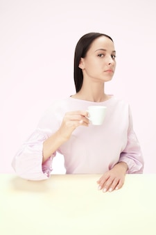 Schöne einsame frau, die im rosa studio sitzt und traurig schaut, die tasse kaffee in der hand haltend. nahaufnahme getöntes porträt im minimalismusstil