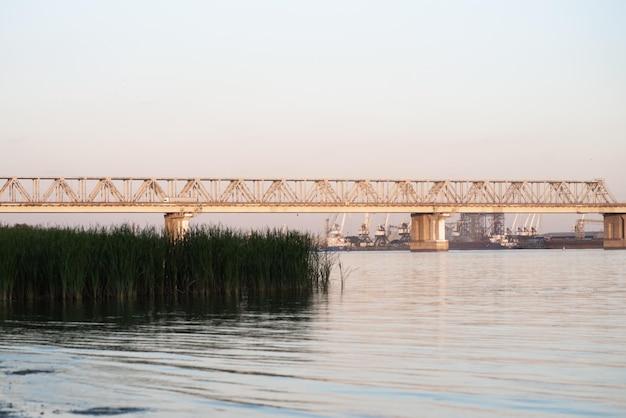 Schöne eisenbahnbrücke im hintergrund der bucht bei sonnenuntergang