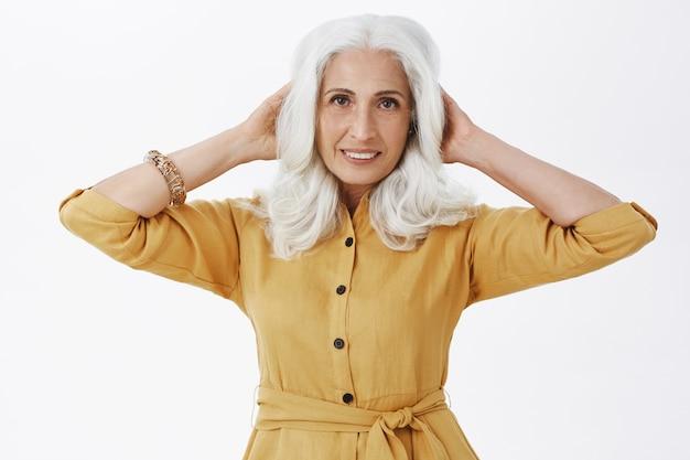 Schöne elegante ältere frau, die mit haarschnitt zufrieden schaut