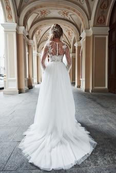 Schöne, elegante braut mit einem perfekten hochzeitskleid, wirft um schöne architektur auf.