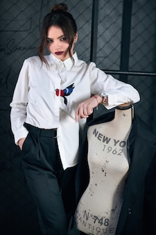 Schöne elegante brunettefrau kleidete in mode den anzug der männer an